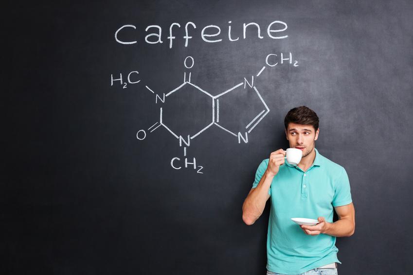 Man drinking coffee over blackboard with structure of caffeine molecule